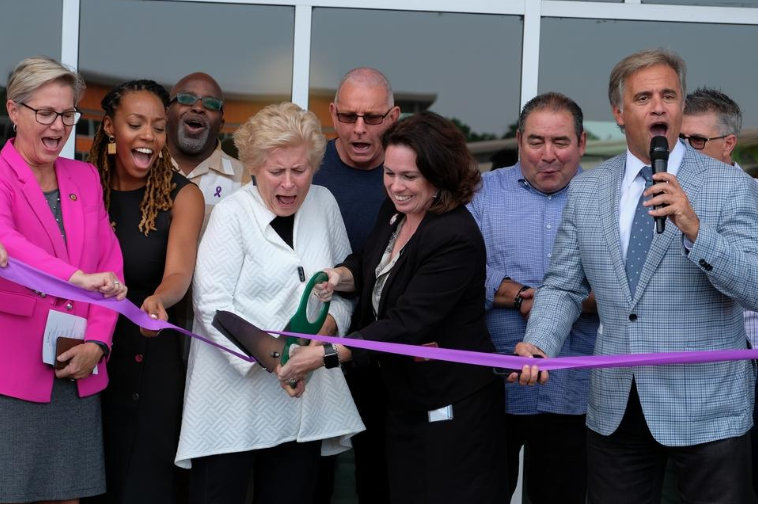 A group of people stand behind a ribbon while a woman cuts the ribbon. Everyone is laughing or smiling.
